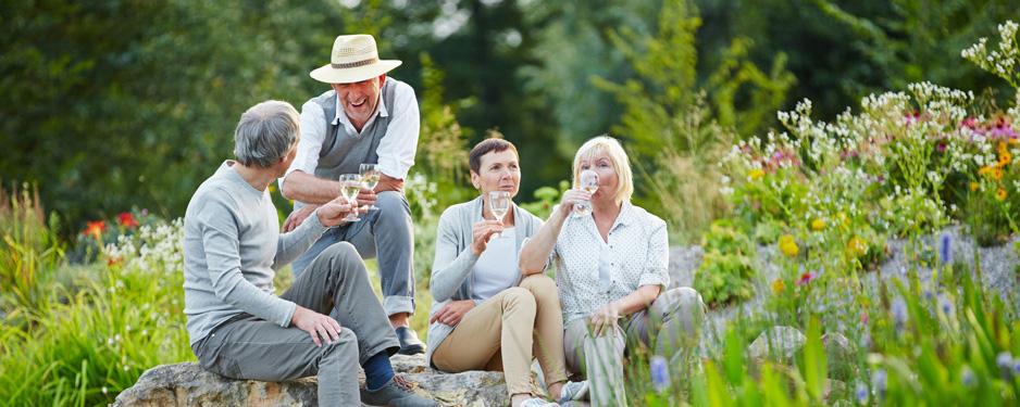 Senioren sitzen Dank Betriebskollektivversicherung entspannt im Garten